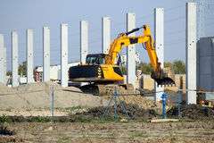 Excavator working on factory construction site Royalty Free Stock Photography