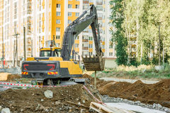 Excavator working outside on road construction Royalty Free Stock Photos