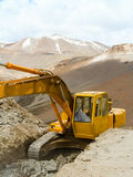 Excavator working on a precipice in the Himalayas Stock Image