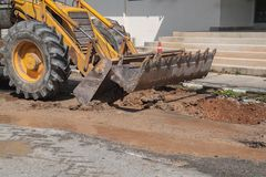 Excavator working on the Repair of pipe water on road Stock Image