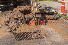 Excavator working on the Repair of  pipe water and sewerage on road Royalty Free Stock Images