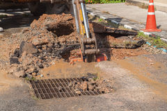 Excavator working on the Repair of  pipe water and sewerage on road Royalty Free Stock Image