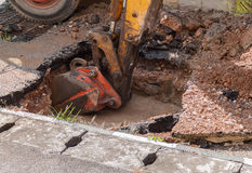Excavator working on the Repair of  pipe water and sewerage on road Stock Photo