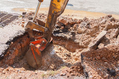 Excavator working on the Repair of  pipe water and sewerage on road Stock Image