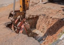 Excavator working the Repair of pipe water sewerage on road Royalty Free Stock Photos