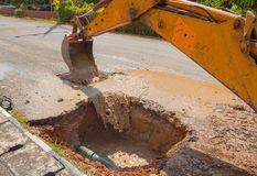 Excavator working the Repair of pipe water sewerage on road Royalty Free Stock Photo