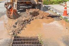 Excavator working on the Repair of pipe water and sewerage on road Stock Images