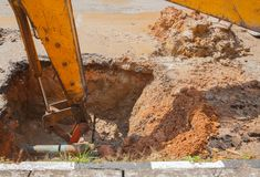 Excavator working on the Repair of pipe water and sewerage on road Royalty Free Stock Photo