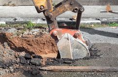 Excavator working on the Repair of  pipe water and sewerage on road Stock Photography