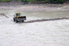 Excavator working in a river Stock Images