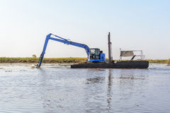 Excavator working in the river Royalty Free Stock Image