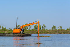 Excavator working in the river Stock Photos