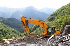 Excavator working on road construction in mountainous terrain Stock Photos
