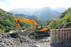 Excavator working on road construction in mountainous terrain Royalty Free Stock Image
