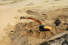 The excavator works in career in a sunny day. POLEWOJE, KALININGRAD REGION, RUSSIA — JUNE 18, 2014: The excavator works in career in a sunny day Stock Photos