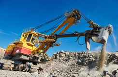 Excavator works with granite or ore at opencast mining Royalty Free Stock Images