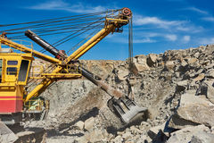 Excavator works with granite or ore at opencast mining Stock Photography