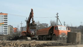 Excavator works on a large construction site. Of a residential apartment house stock video
