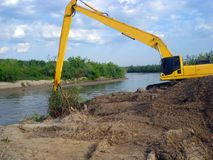 The excavator works on the river. The excavator excavating in river Stock Photography