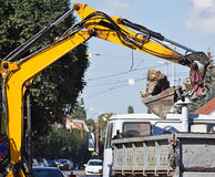 Excavator works at the road construction Stock Image
