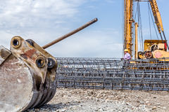 Excavator's bucket and shovel in front of skeleton reinforcing s Stock Image