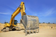 Excavator yellow vehicle on sand quarry Stock Photos