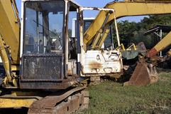 Used excavators, heavy scrap. Used excavators, diggers, heavy scrap, trees and blue sky Royalty Free Stock Photos