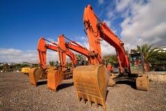 Excavators. Three orange excavators on a day off Royalty Free Stock Photography