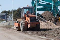 Excavators and asphalt compactor truck Stock Photos