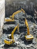 Excavators Baggers digging at a construction site. Excavators dig at a construction site of a street and a subway. Baggers transport dirt to a higher level to stock images
