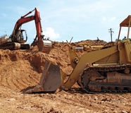 Excavators on Construction Site. Earth moving excavators set against vibrant exposed red clay soil on a construction site Stock Photography