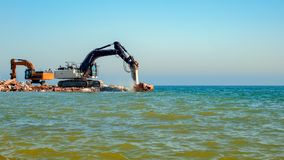 Excavators crashing concrete into the sea. With blue sky royalty free stock photo