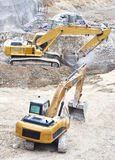 Excavators digging. Closeup of two excavators digging Royalty Free Stock Photography
