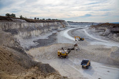 Excavators and dump trucks working and extracting the chalk in a Royalty Free Stock Photography