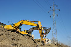 Excavators excavating on site. Picture of lateral view of twoexcavators who excavating on site near town district royalty free stock image
