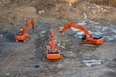 Excavators in mourning. Excavators around piles of broken stones Royalty Free Stock Photos