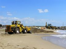 Excavators repairing a beach. Excavators spreading sand on the beach to repair it after a storm Stock Photos