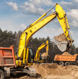 Excavators ship sand in trucks on road construction.  Royalty Free Stock Images