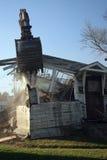 Excavatrice déchirant une maison Photos stock