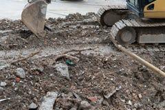 Excavatrice démolissant des débris de béton et de blocaille de brique Image libre de droits