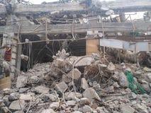 Excavatrice démolissant des débris de béton et de blocaille de brique Photos stock