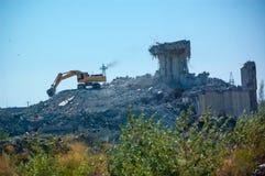 Excavatrice démolissant un vieux bâtiment, la démolition du bâtiment photo libre de droits