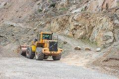Excavatrice d'exploitation dans le puits en pierre Photographie stock