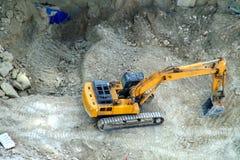 Excavatrice dans l'action sur un chantier de construction images libres de droits