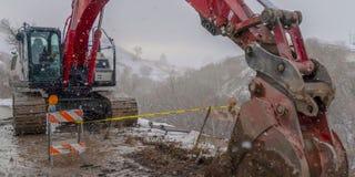 Excavatrice et barricade rouges de panorama sur une route boueuse de montagne vue en hiver image libre de droits