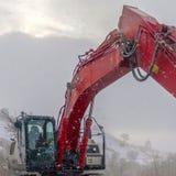 Excavatrice et barricade rouges de place sur une route boueuse de montagne vue en hiver photographie stock libre de droits