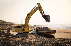 Excavatrice et camion à benne basculante à la plage photographie stock