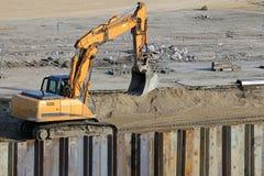 Excavatrice fonctionnant au chantier de construction Image libre de droits