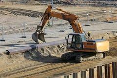 Excavatrice fonctionnant au chantier de construction Photo libre de droits