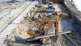 Excavatrice fonctionnant au chantier de construction Photos stock
